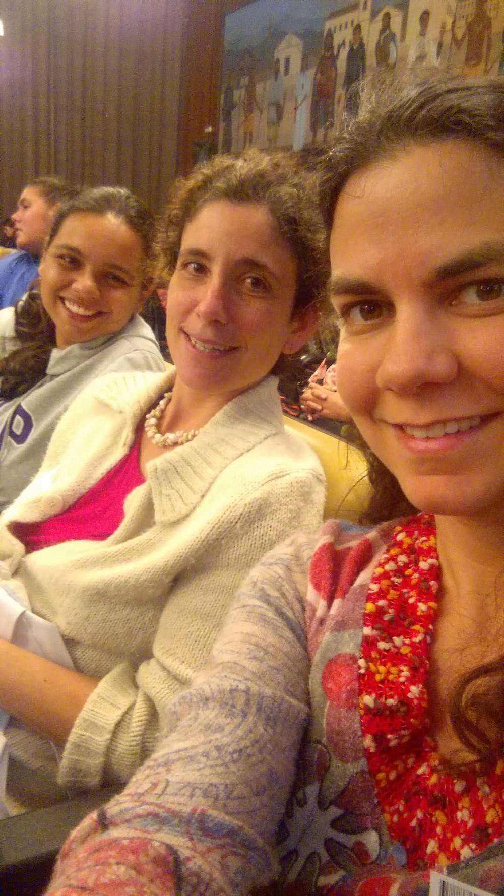 Três mulheres sentadas lado a lado no auditório