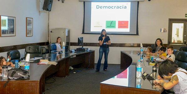 """Mães e crianças assistindo uma apresentação numa sala da Câmara dos Vereadores da Cidade de São Paulo. O slide que está sendo apresentado em escrito em destaque a palavra """"democracia"""". Há duas mulheres apresentanado. Uma crianças a esquerda, 4 a direita e uma mãe com um bebê no colo próxima a mulher que apresenta."""