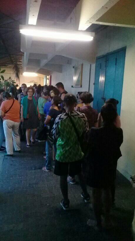 Muitas pessoas numa fila de pé num corredor