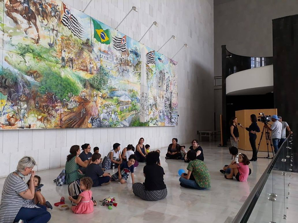 Mães e crianças sentadas no chão do hall monumental da assembleia legislativa. Há um enorme quadro ao fundo. Paredes e pisos são de mármore branco.