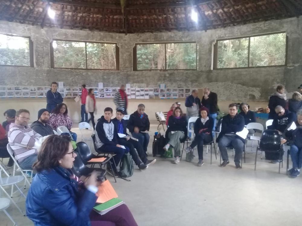 Pessoas sentadas em cadeiras no formato de circulo