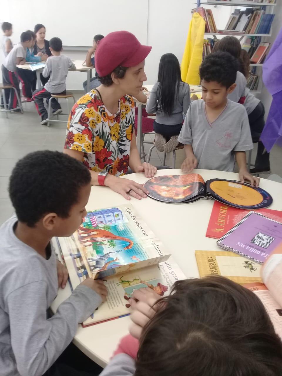 Uma mulher e 3 crianças de uniforme escolar sentados em torno de uma mesa. Há 5 livros em cima da mesa. A mulher lê para uma das crianças e as outras crianças olham os outros livros