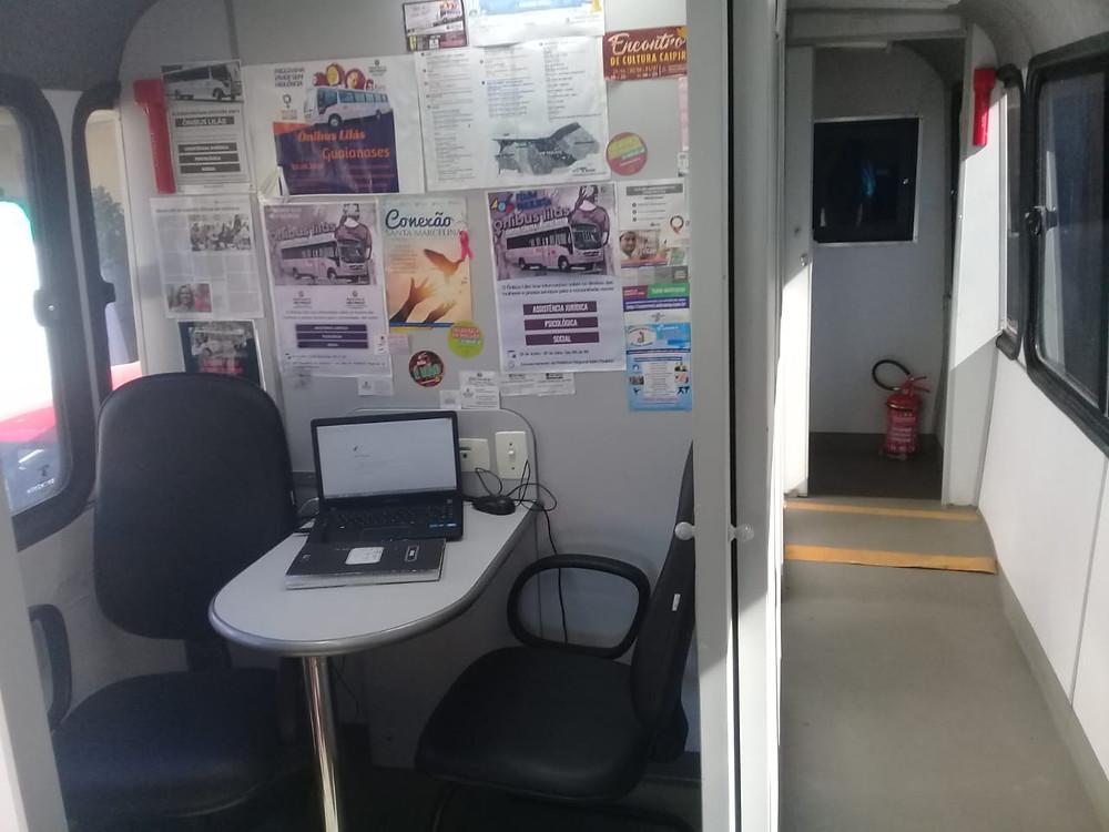 Parte interna do ônibus Lilás, com uma mesa pequena com um computador ao centro e duas cadeiras