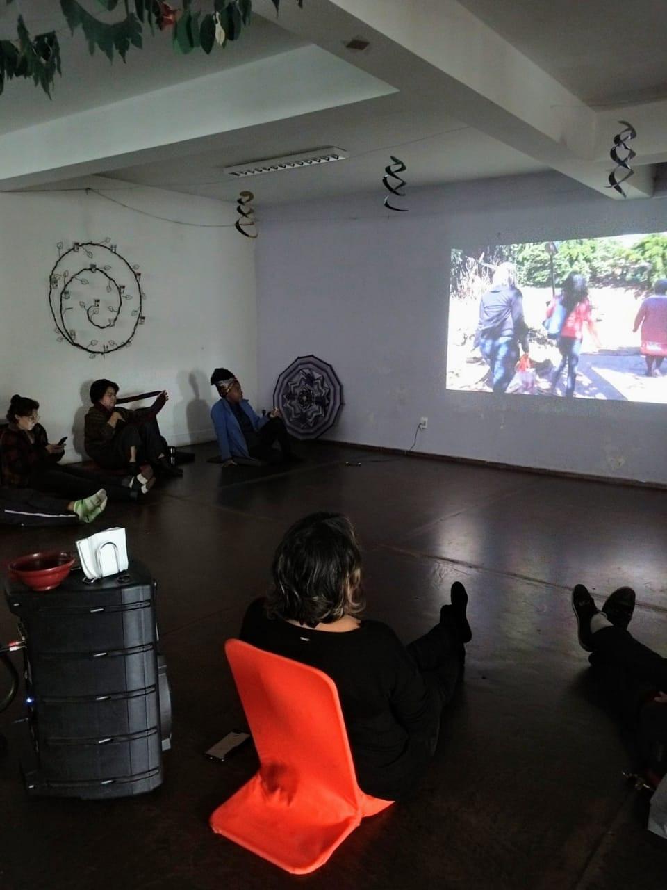Pessoas sentadas no chão assistindo um filme projetado na parede