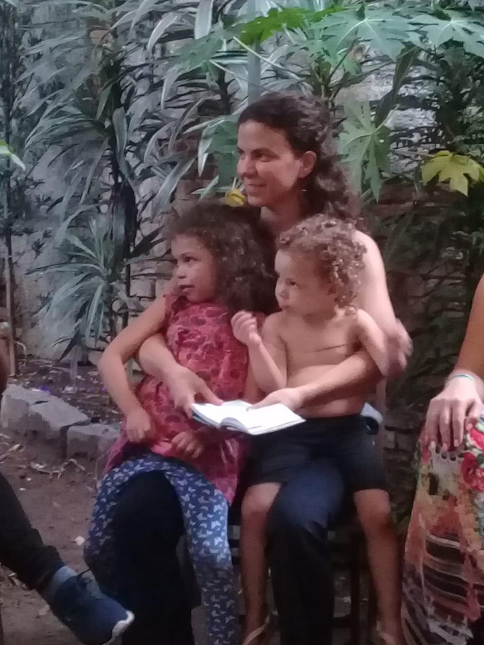 Mãe sentada numa cadeira com duas crianças no colo, segurando um caderno de anotações