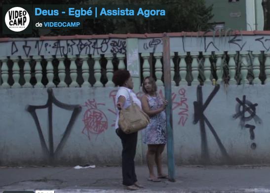 Duas mulheres esperam ônibus num ponto de ônibus
