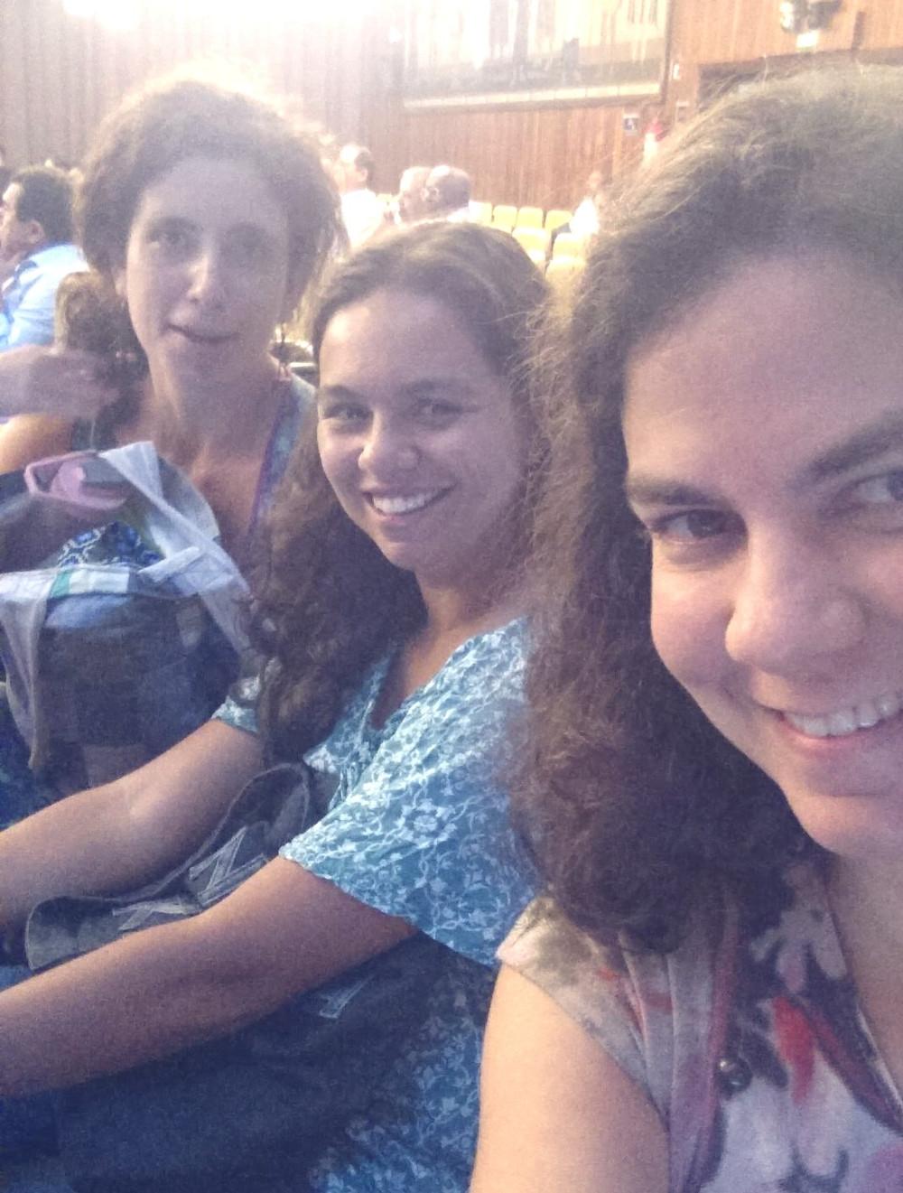 três mulheres sentadas lado a lado num auditória