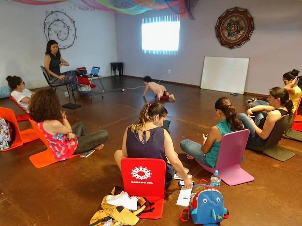 6 mulheres sentadas no chão em cadeiras com apoio para as costas de diversas cores. Uma criança engatinha em direção da mulher que está utilizando o computador e fazendo a mudança dos slides. O teto e enfeitado com tecidos coloridos e o piso é de madeira.