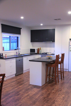 Contrasting white and dark grey black cupboards in kitchen.