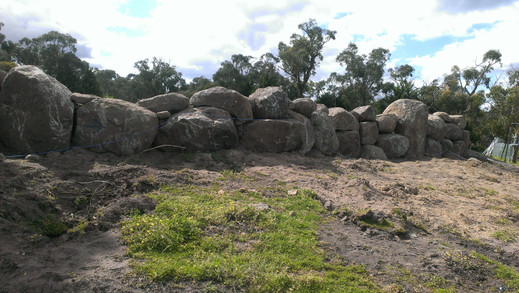Retaining wall with excavated rocks