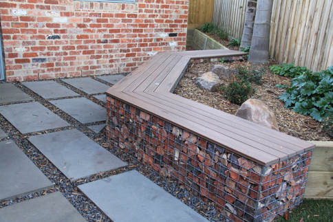 Red recycled brick offcuts used for a gabion seat and small retaining wall.