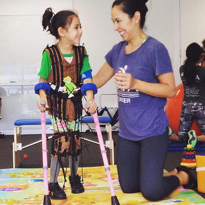 Young girl in crutches with therapist