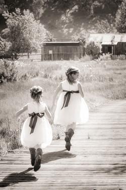 flowergirls running over bridge