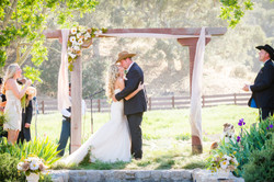 rustic first kiss under arch