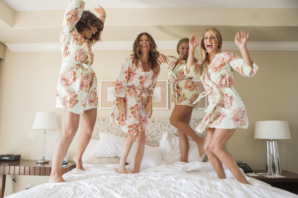 Fun bridesmaids jumping on bed