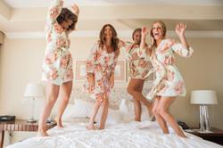 Fun bridesmaids jumping on bed