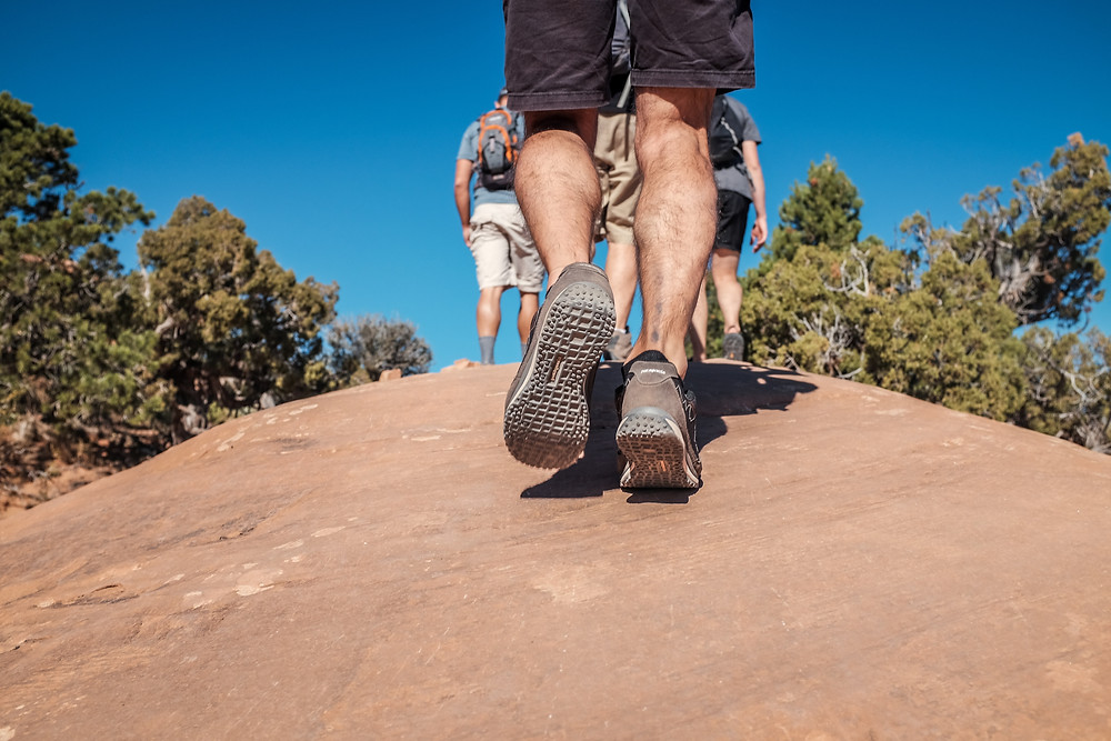 Hikers approaching top of the hill. Close up image of male leg calf
