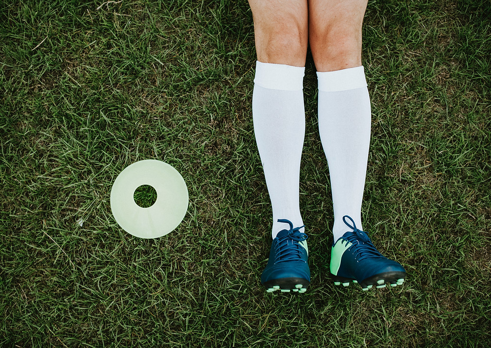 Athlete laying on green grass wearing white compression socks