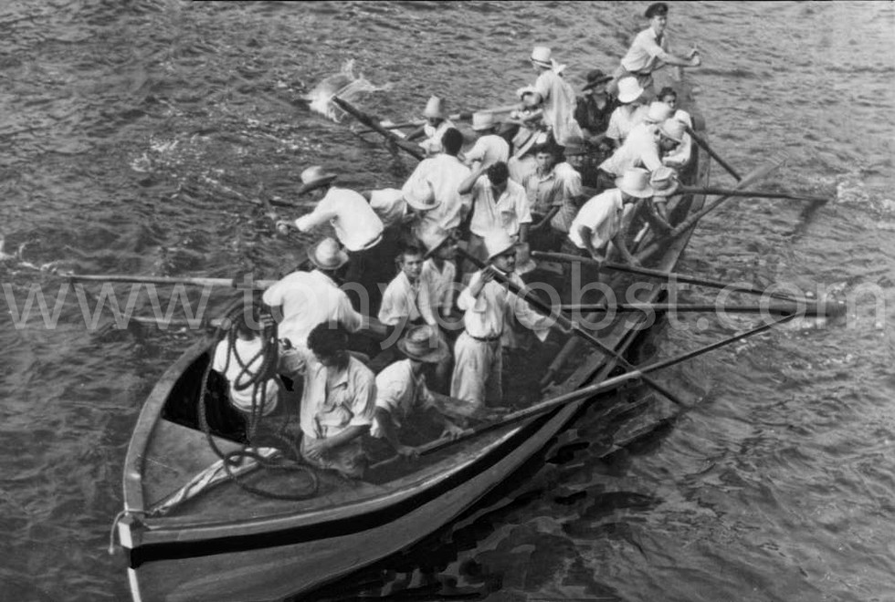 1940 Feb 20. Andrew at the helm. Everson holding the oar  in the front looking at camera with the white hat