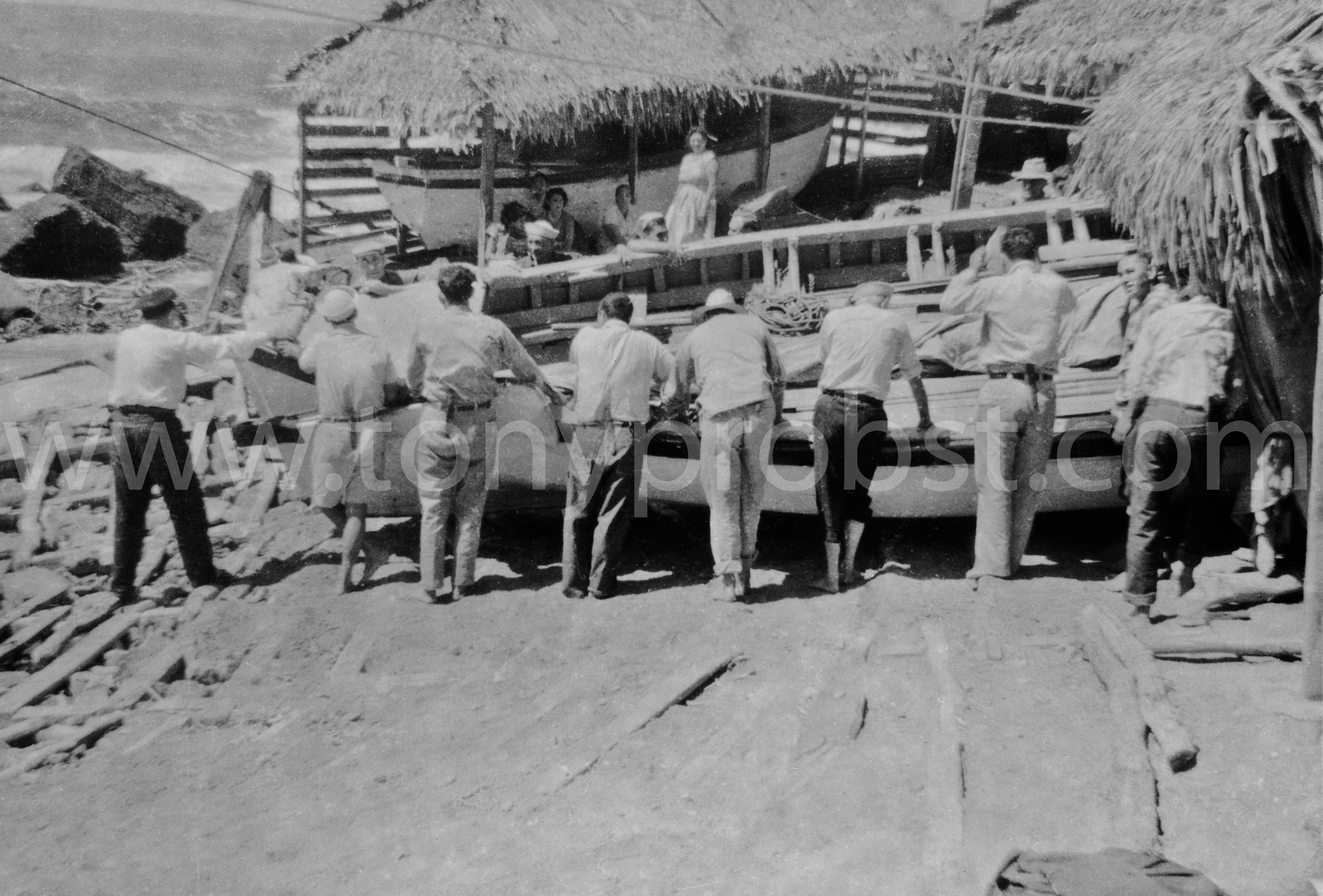 1961 July, Getting ready to pull Longboat into Bounty Bay. Chrissty, Warren, Elwin, Ivan, Melvin, Pastors wife Mrs. Davis standing in the back