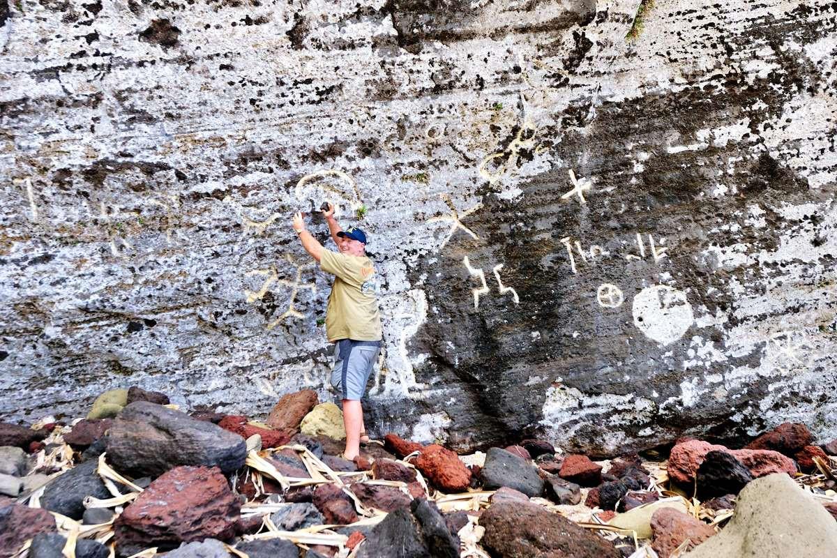 Tony Probst adding his own mark to the petroglyphs on Pitcairn Island