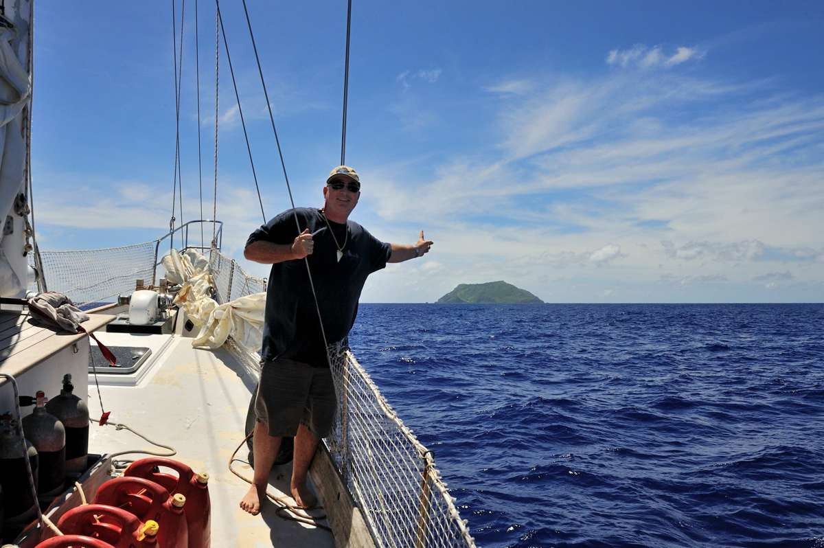 Tony Probst pointing to to most remote populated place on planet Earth, Pitcairn Island