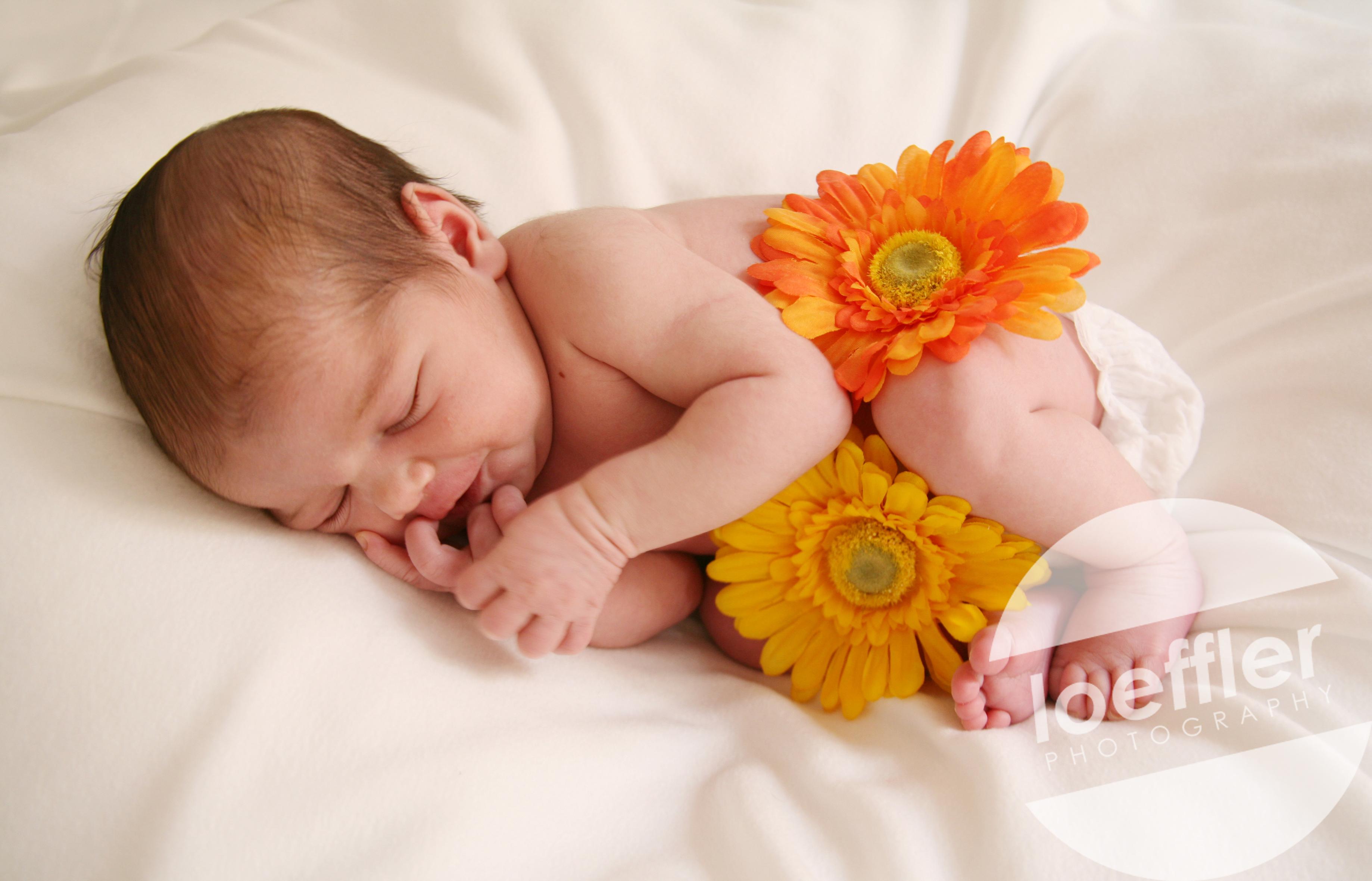 Nouveau-né souriant avec fleurs