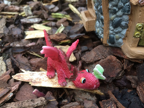 Miniature red dragon playing with a butterfly