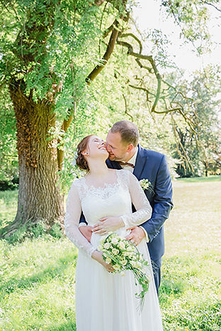 Brautpaar umarmt sich im Grünen
