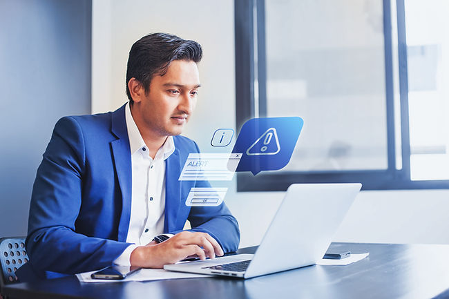 Indian man receiving alert notification in financial fraud protection software on his comp