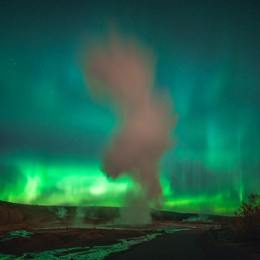 Erupting geyser under aurora