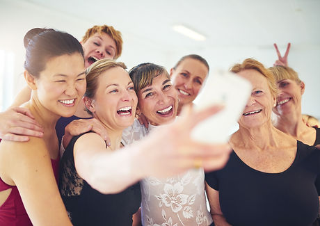 Laughing group of senior women standing arm in arm together taking a selfie with their dan