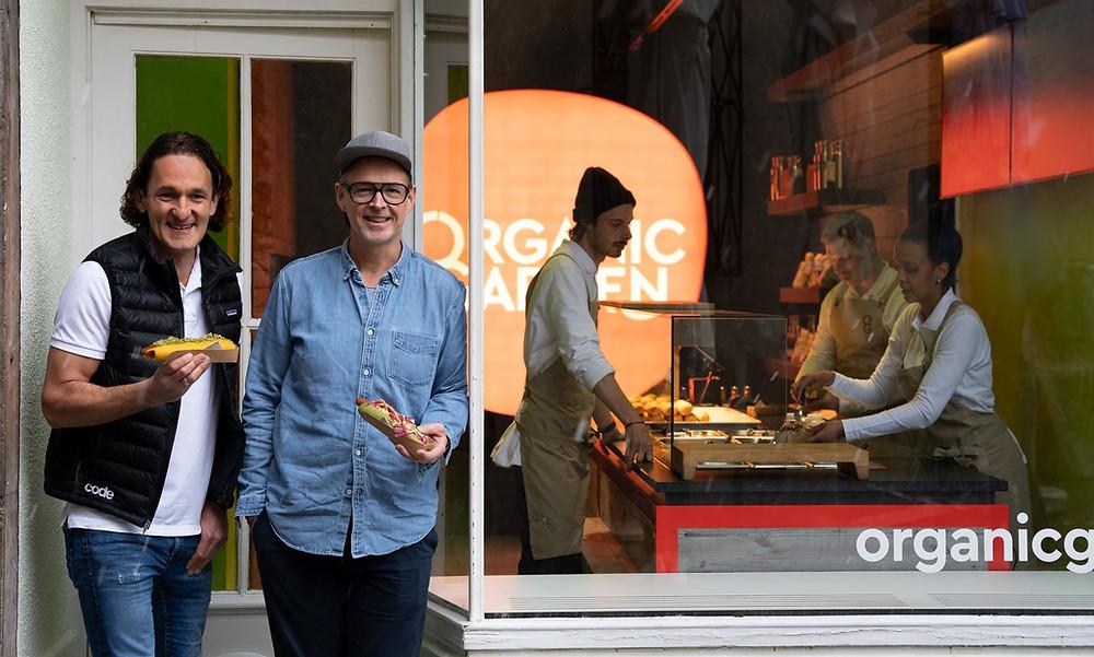 Holger Stromberg und Martin Wild stehen vor dem Organic Garden Signature Store, jeweils mit einem Hotdog in der Hand.