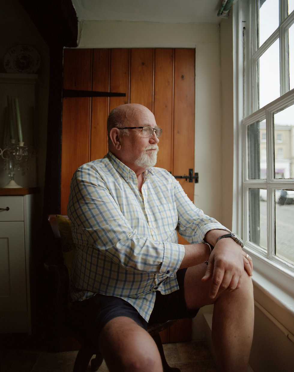 An older man sitting close to the window looking outside