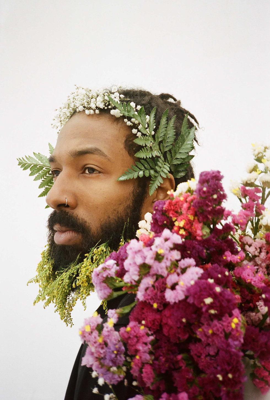 Portrait of a man wearing a flower crown