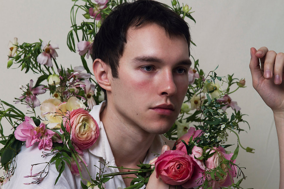 Portrait of a man blushing surrounded by many flowers
