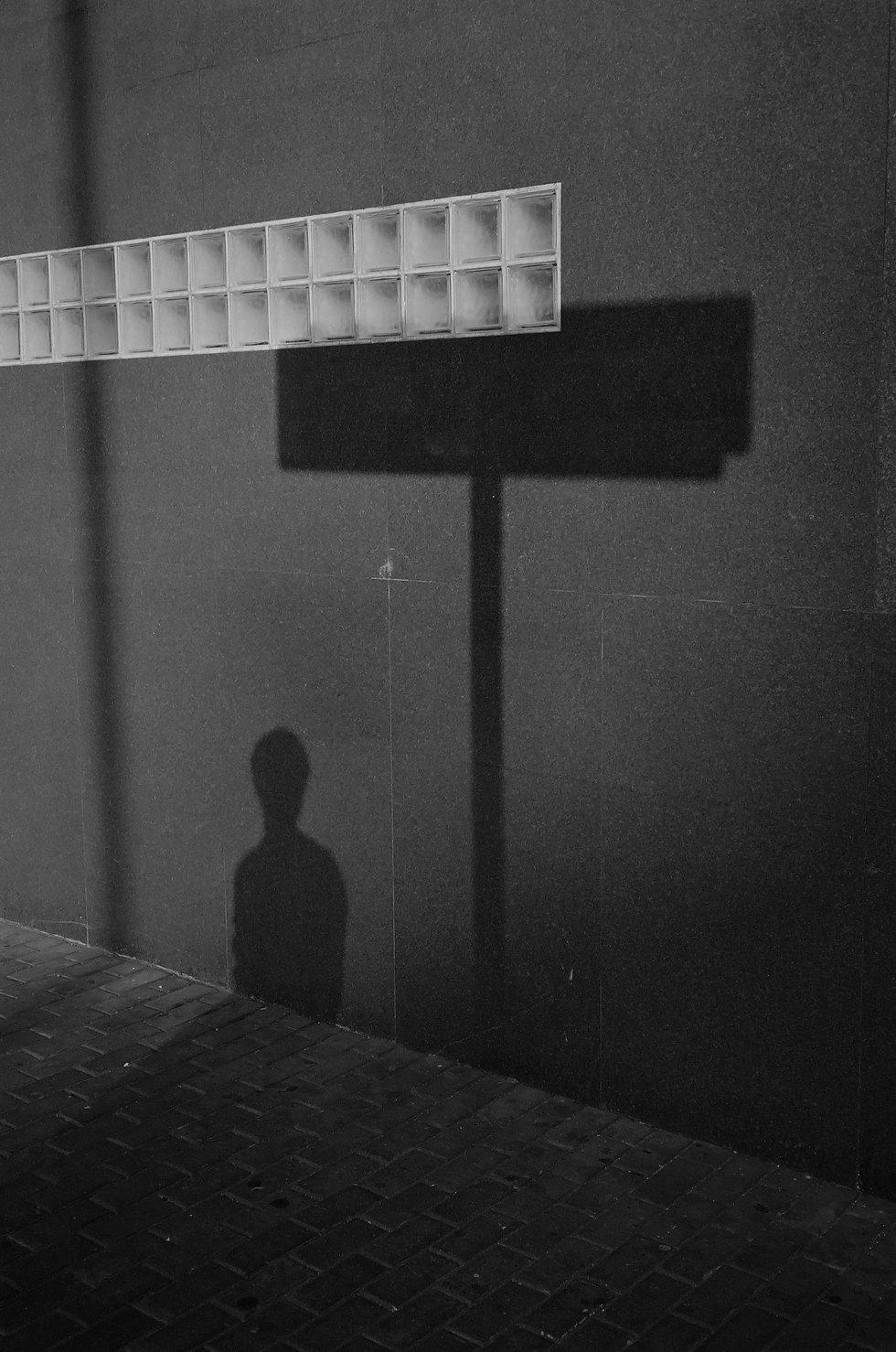 Shadow of a boy figure over a black wall
