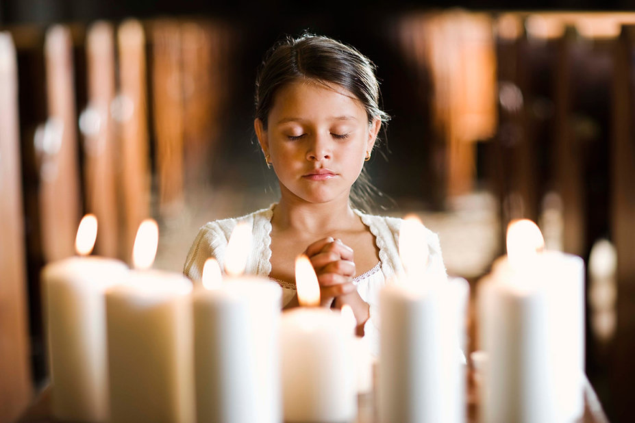 A young girl kneeling before the alter with hands together amd eyes closed in pray.