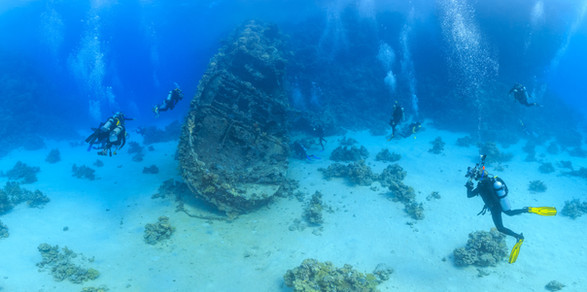 Scuba divers underwater with ship wreck