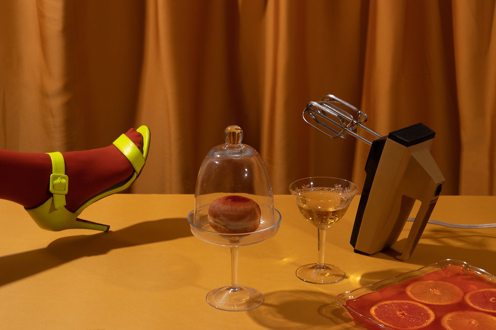 Composition of female feet wearing high heel shoe and a donut in a glass  fancy plate