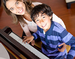 Piano teacher hugging student at the piano, smiling and looking up at camera