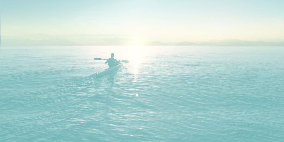 Business coach paddling his kayak on a smooth lake as the sun rises
