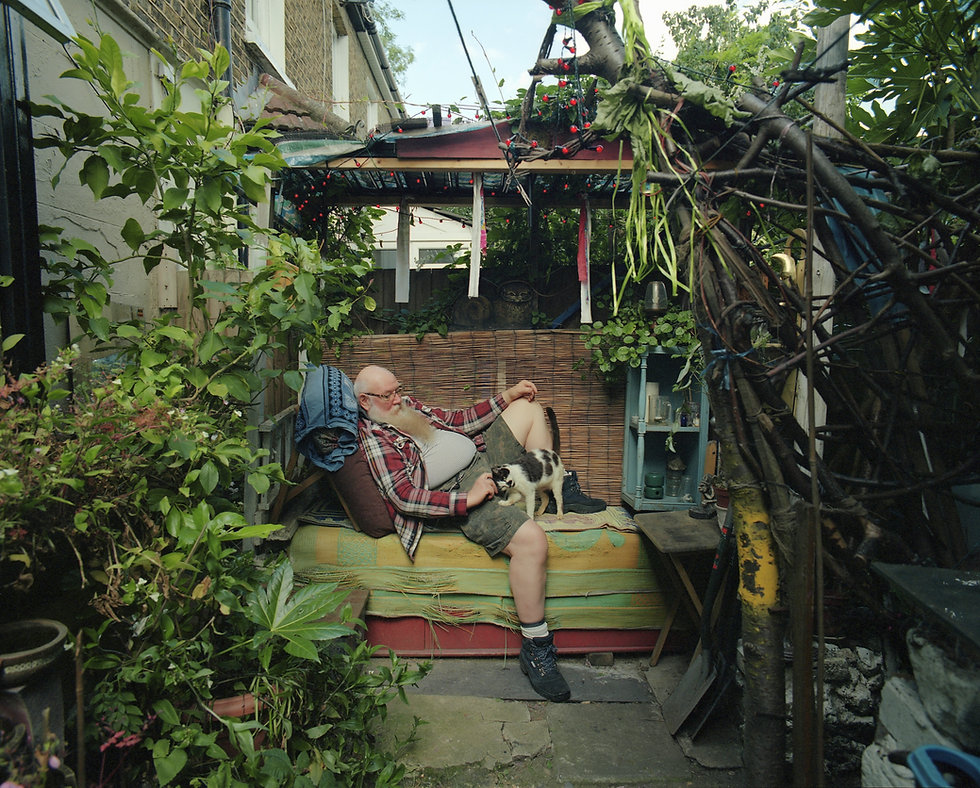 A man with a long white beard sitting at his cozy backyard