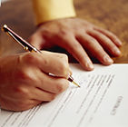 hands signing real estate contract