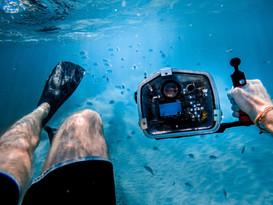 Scuba diver holding camera underwater
