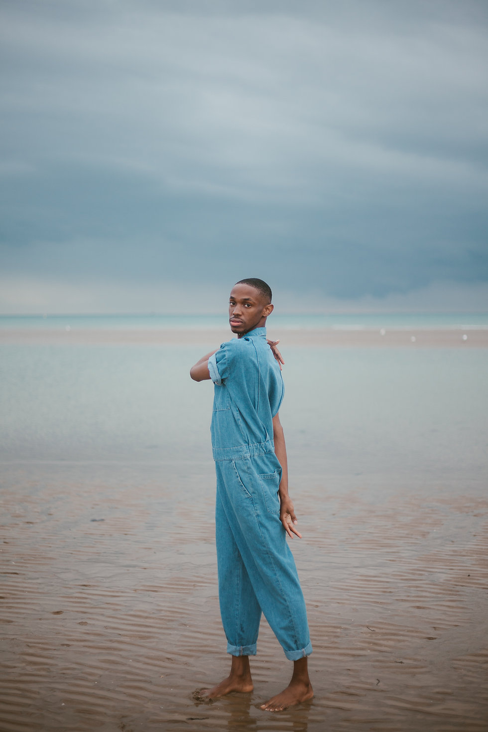A young man is standing on the seashore in a denim jumpsuit