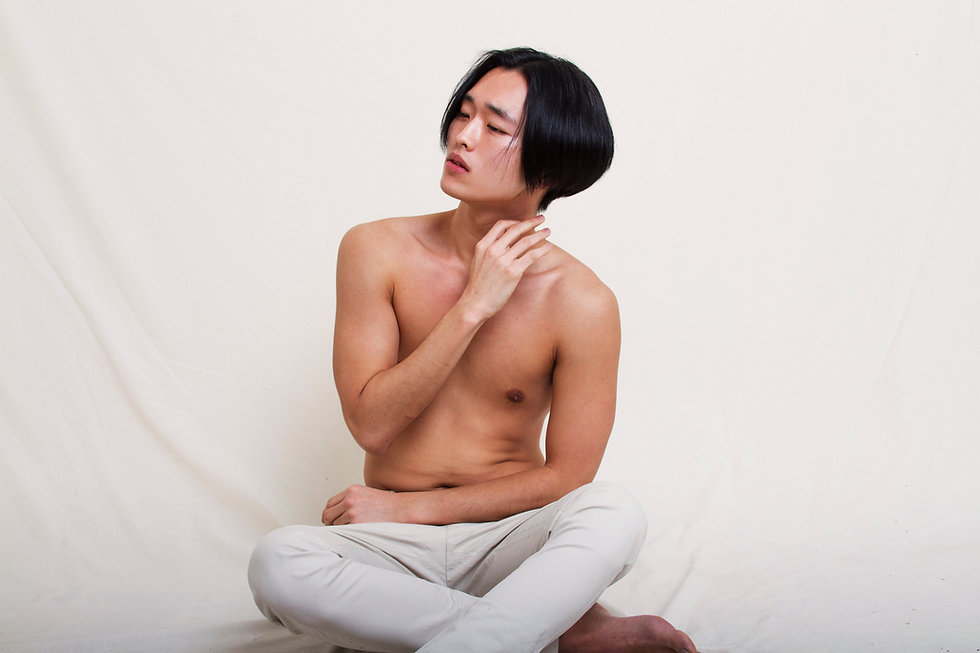 A young man sits in front of a white textile background with a sad expression