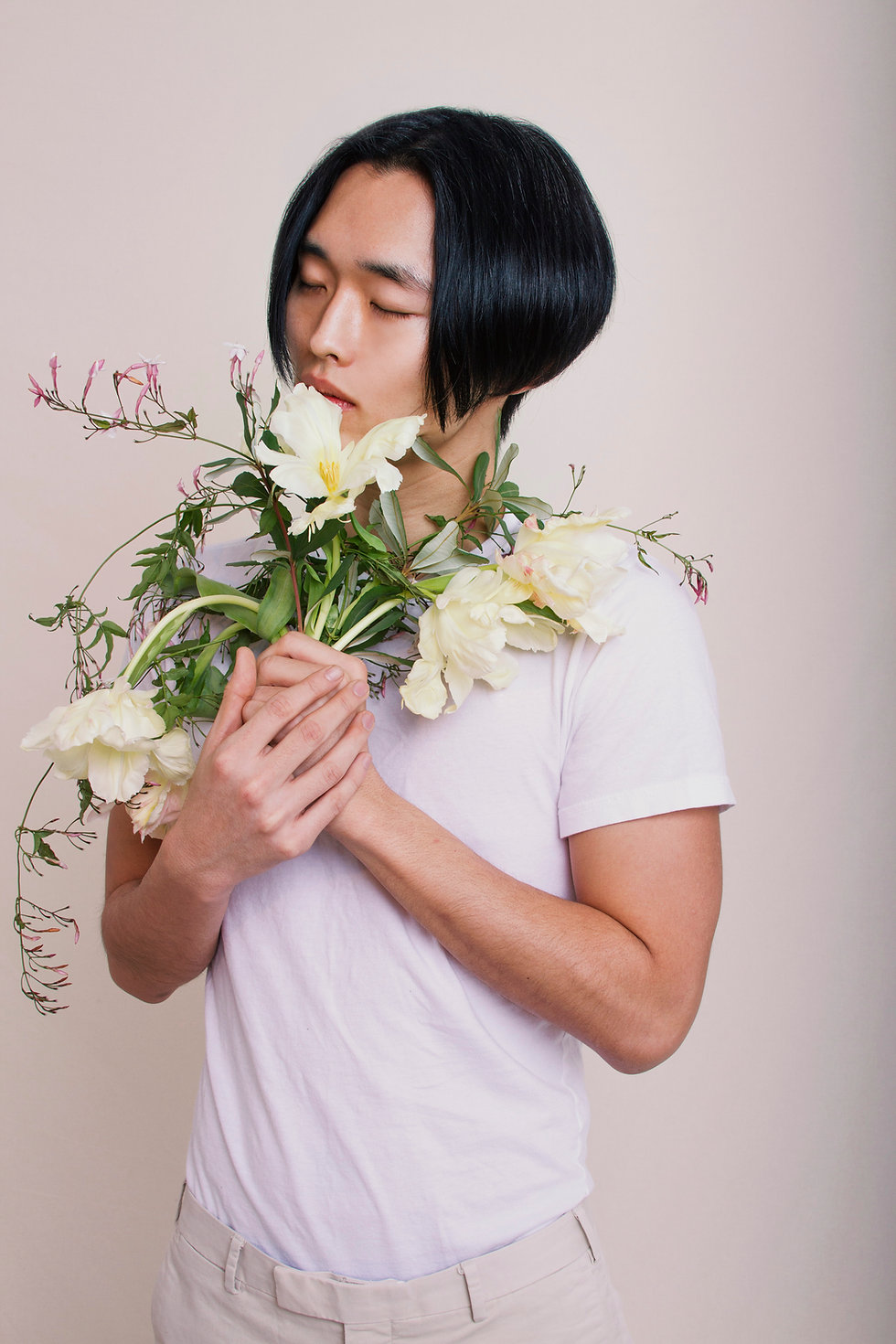 A young man smelling a bouquet of flowers with his eyes shut