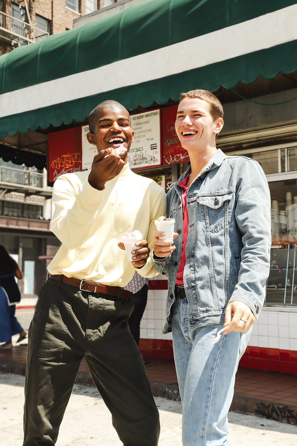 Two young boys standing in front of a deli eating ice cream