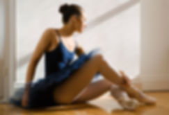 Young girl in navy tutu and pointe shoes